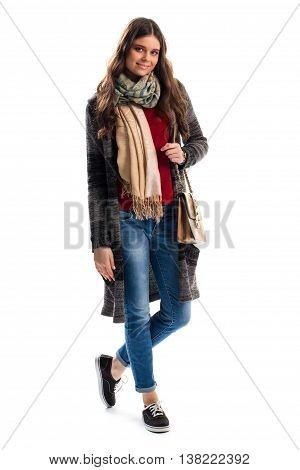 Woman in sweater coat smiling. Beige scarf and black shoes. New stylish outerwear for spring. Feel warm and comfortable.