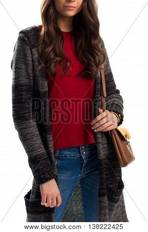 Woman in long sweater coat. Denim pants and handbag. Fashionable outerwear of wool. Warm natural fabric.