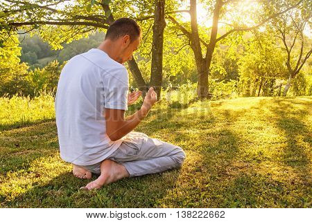 Young Muslim Man Pray In Nature At Sunset Time