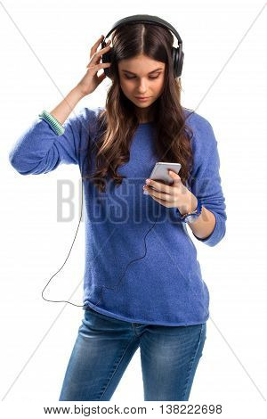 Lady in headphones holds phone. Blue watch and sweater. Girl tests new headphones. This music sounds unbelievable.