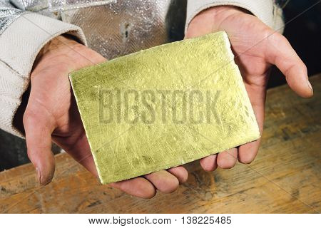 Raw gold ingot in hands just made at a factory