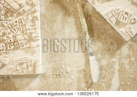 Plaster-coated Knife Between 3D City Map Plaster Models