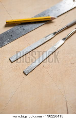 Rasps, Pencil, And Metal Rule On Wooden Surface