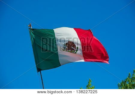 Mexican flag weaving on clear blue sky