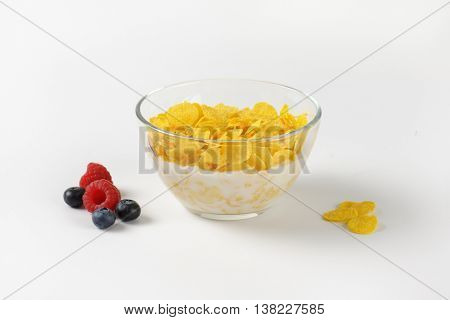 bowl of corn flakes with fresh milk on off-white background with shadows