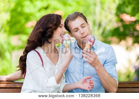 Young couple eating an icecream at the park