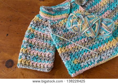 Crocheted baby sweater with a crochet hook and skein of yarn.