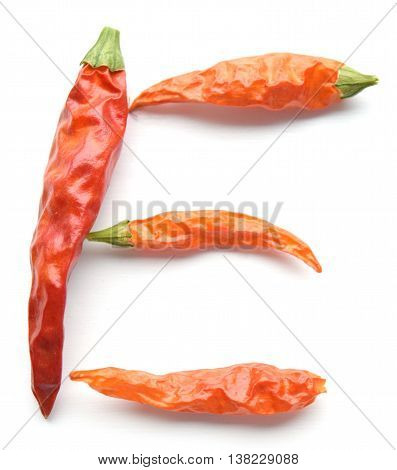Dried red cayenne chili peppers organized in the shape of the letter E - isolated