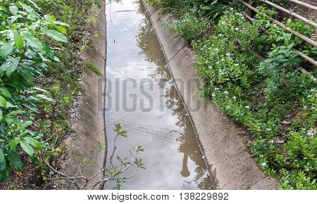 Small concrete ditch in front of the countryside village in Thailand.