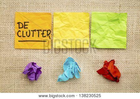 declutter concept - colorful sticky notes against burlap canvas