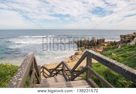 View from the wooden boardwalk overlooking the scenic Indian Ocean, limestone rock formations and beach at Penguin Island in Rockingham, Western Australia.