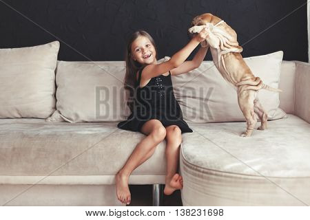 Home portrait of cute child hugging with puppy of Chinese Shar Pei dog on the sofa against black wall