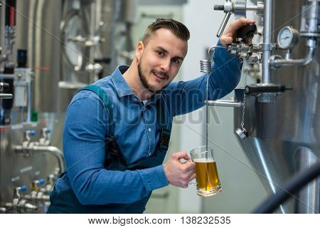 Portrait of happy brewer testing beer from tank at brewery