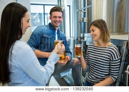 Happy brewers having beer at brewery