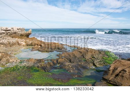 Tide pools with algae, limestone rock and Indian Ocean seascape under a blue sky with clouds at Penguin Island in Rockingham, Western Australia.