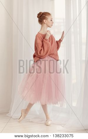 Pretty young ballerina drinking coffee standing at the window. The girl is sad. Ballerina in tutu and pink sweater