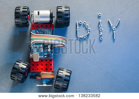 Handmade toy-machine on microcontroller base, blue background, diy concept. Homemade construction with electrical elements. Do-it-yourself plaything prototype, made with electronic components