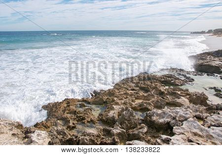 Foamy Indian Ocean waves with seascape under a blue sky with clouds at Penguin Island's remote, rocky beach in Rockingham, Western Australia.