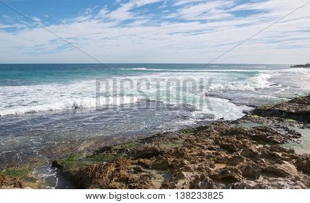 Indian Ocean waters rushing the rocky beach under a blue sky with clouds at Penguin Island in Rockingham, Western Australia.