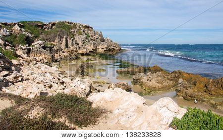 Indian Ocean seascape with rugged limestone bluffs and native flora under a blue sky with clouds at Penguin Island in Rockingham, Western Australia.