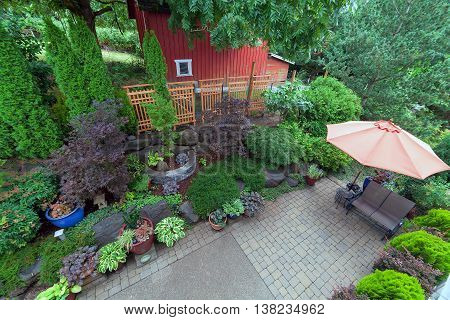 Backyard garden landscaping with paver bricks patio hardscape trees potted plants shrubs pond rocks furniture and red barn