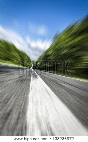 The white line on the road receding into the distance close up at high speed