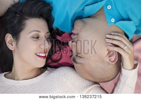 Engaged latino couple laying on a park looking carefree happy and in love