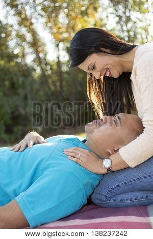 Young hispanic couple on a romantic outdoor picnic date in a park