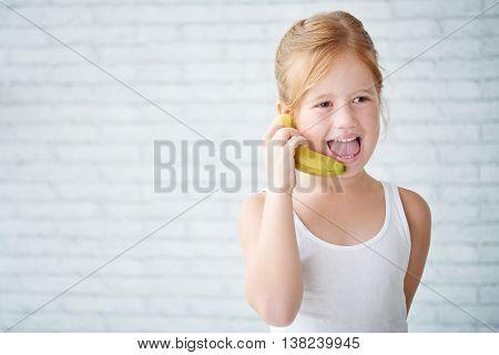 Cheerful little girl using banana instead of phone