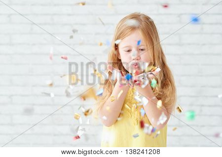 Little girl blowing out confetti in in her hands