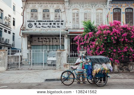 GEORGE TOWN MALAYSIA - MARCH 22: Vendor sells snacks from the tricycle in UNESCO Heritage buffer zone in George Town Penang Malaysia on March 22 2016.