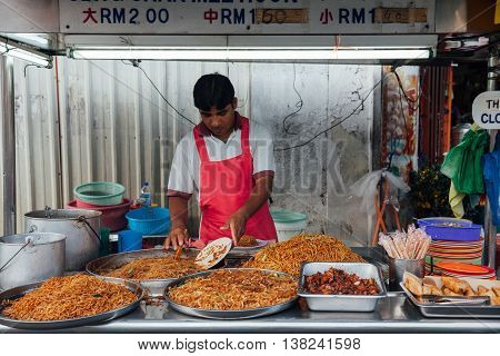 GEORGE TOWN MALAYSIA - MARCH 22: Man sells kway teow noodles at the Kimberly Street Food Night Market on March 22 2016 in George Town Penang Malaysia.