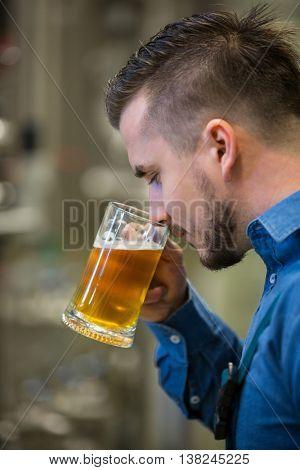 Close-up of brewer testing beer at bewery