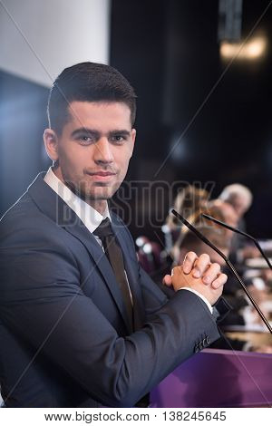 Portrait of a young professionally-looking man sitting at a conference table