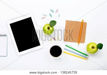 Design workspace. tablet notebook colored pencils paper clips green apple and cup of black coffee on a white background. top view flat lay