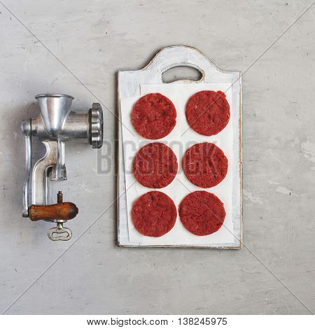 Beef cutlets for burgers with vintage meat grinder on a white surface top view