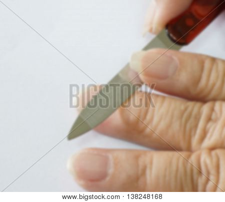 Blur of old woman hand with metal nail file