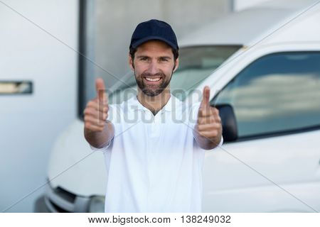 Portrait of delivery man is posing and smiling with thumbs up in front of a warehouse