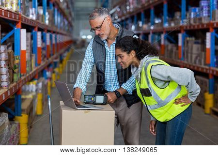 Manager showing something on a laptop to a worker in a warehouse