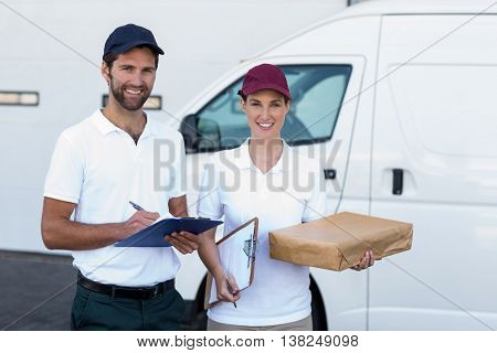 Portrait of delivery people are holding goods and smiling to the camera in front of a warehouse