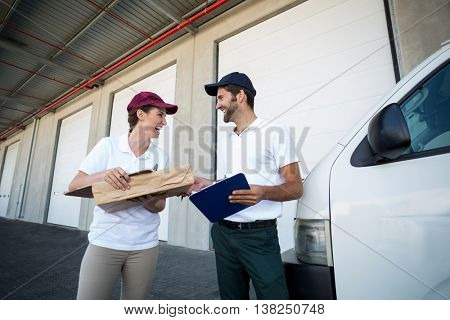 Low angle view of delivery people are looking each other and laughing in front of a warehouse