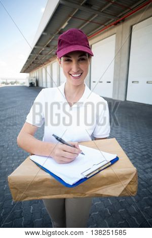 Portrait of delivery woman is holding a cardboard box and smiling to the camera in front of a warehouse