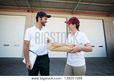 Portrait of delivery people are holding a cardboard box in front of a warehouse