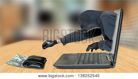 Anonymous hacker is stealing money from table.