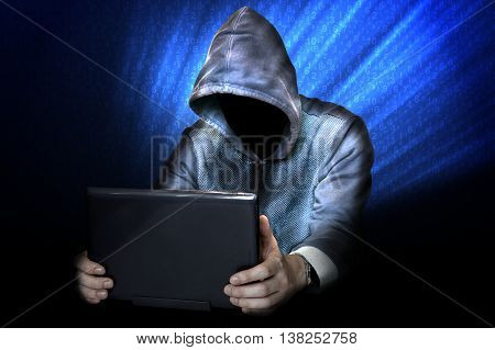 Anonymous hacker is using laptop at night.