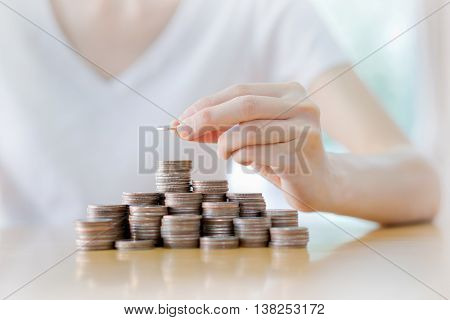 Close-up Of Businesswoman Putting Coin To Rising Stack Of Coins