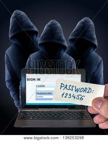 Phishing concept. Anonymous hackers behind notebook with login screen.
