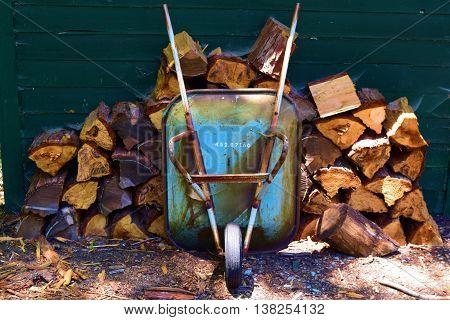 Wheelbarrow next to a pile of wood taken in a residential backyard