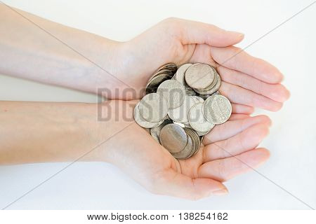money and finances concept - close up of womans cupped hands showing coins