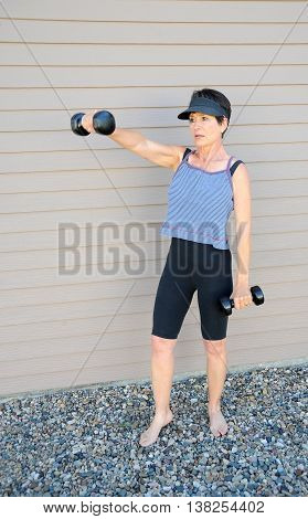 Mature female beauty using hand weights to keep in shape.